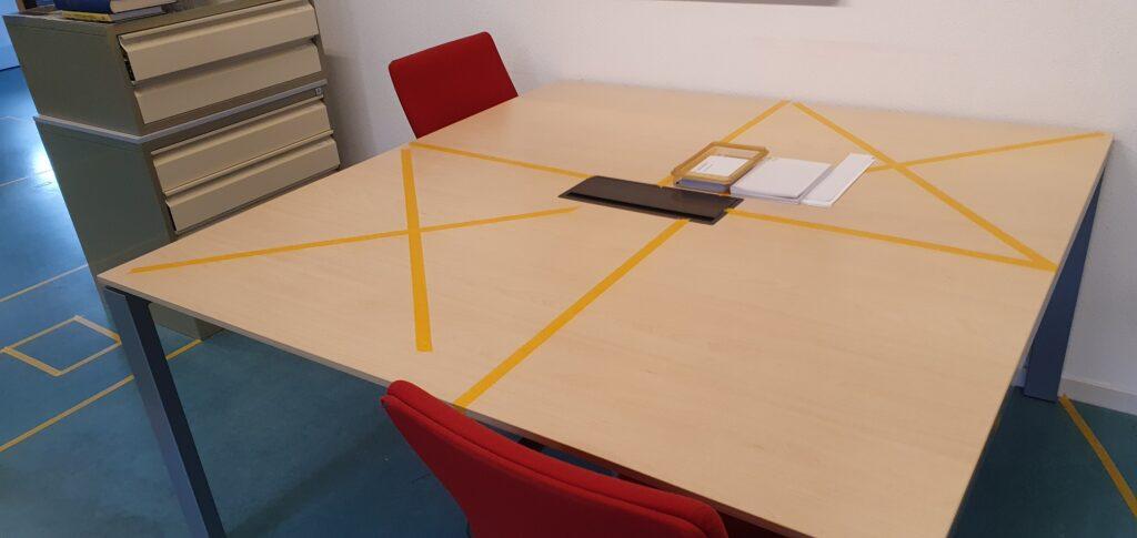 Tafels op de studiezaal met beperkte zitruimte, aangegeven middels oranje kruizen op de tafel.