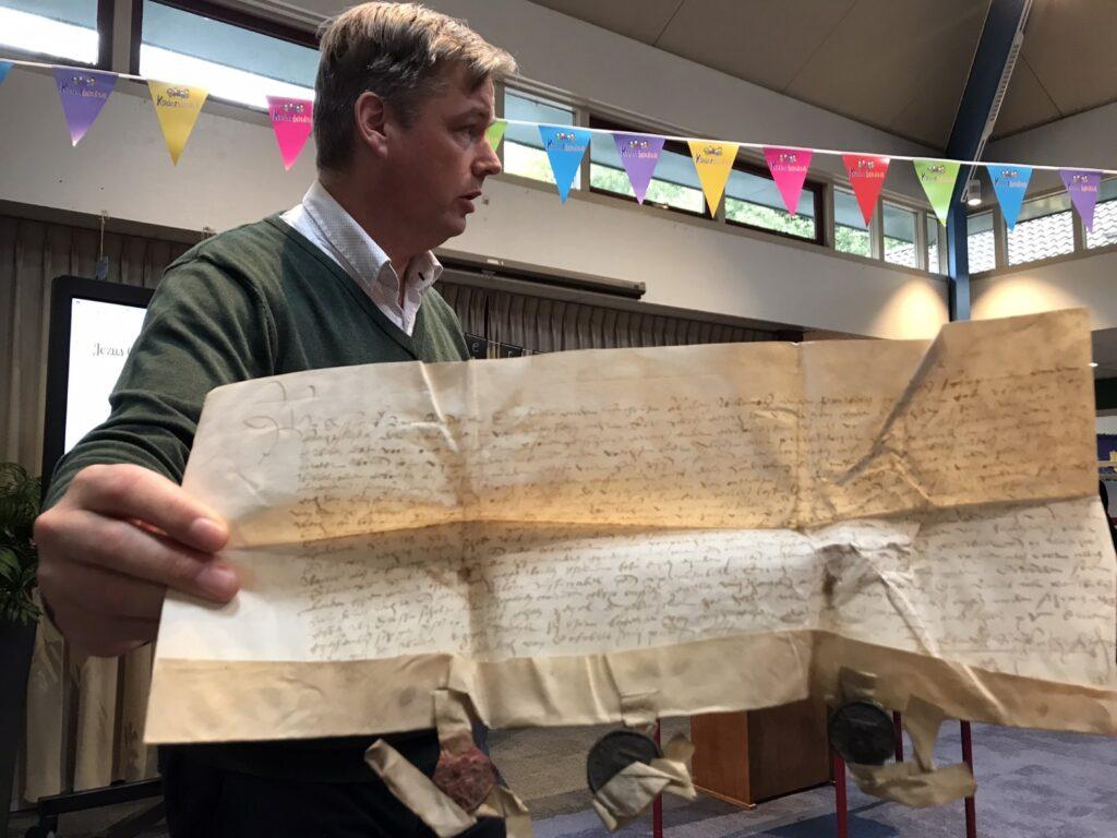 Dhr. Postema laat een oud archiefstuk zien. Foto C. Molhoek