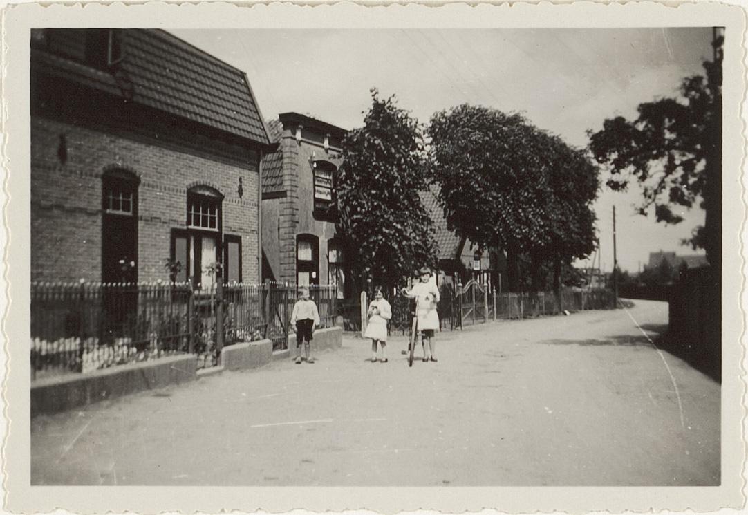 Gedeelte van de Vlierweg gezien naar het oosten met links enkele van de woningen aan de noordzijde van de weg. Op de weg staan drie kinderenTopografisch-Historische Atlas Houten, Schalkwijk en Tull en 't Waal, Cat# 41146